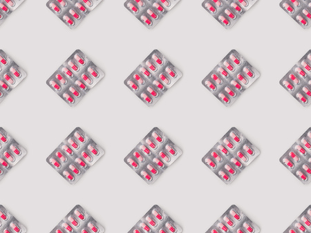Set of blister packs with red and pink pills isolated on white