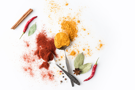 crossed spoons with paprika and curry isolated on white Stok Fotoğraf