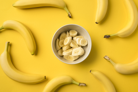 Top view of Plate with cut ripe bananas isolated on yellow