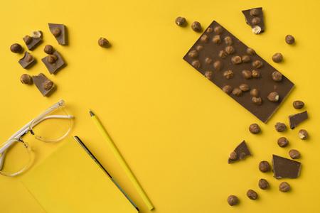 연필과 노란색에 고립 된 초콜릿 노트북의 상위 뷰