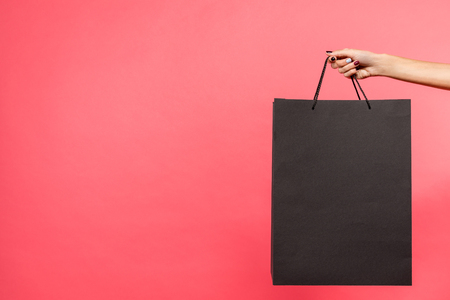 cropped shot of woman holding black shopping bag isolated on red Reklamní fotografie