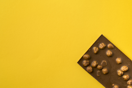 Top view of chocolate bar with nuts isolated on yellow