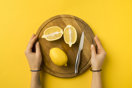 cropped image of woman holding wooden board with lemons isolated on yellow