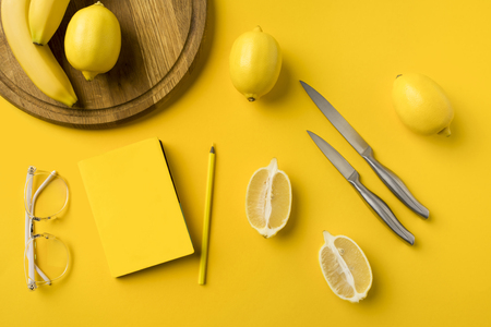 Top view of lemons, knifes, notebook and pencil isolated on yellow Stock Photo