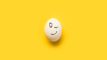 Painted egg with winking emoji isolated on yellow