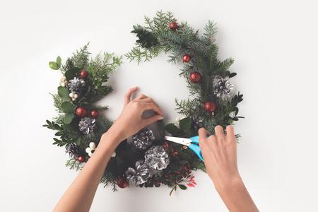 bijgesneden weergave van de hand maken van de kroon van Kerstmis van dennentakken, kerstballen en dennenappels met wenskaart, geïsoleerd op wit