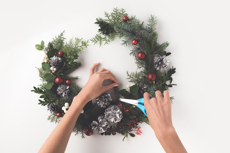 cropped view of hand making christmas wreath from fir branches, christmas balls and pine cones with greeting card, isolated on white Archivio Fotografico