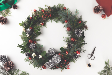top view of christmas wreath made of fir branches, christmas balls and pine cones with envelope, isolated on white