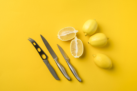 Top view of lemons and knifes isolated on yellow