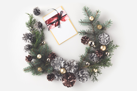 christmas wreath made of fir branches, christmas balls and pine cones with greeting card, isolated on white