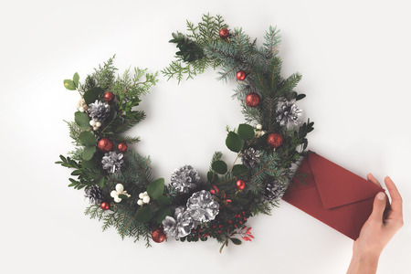 cropped view of hand with christmas wreath made of fir branches, christmas balls and pine cones with envelope, isolated on white