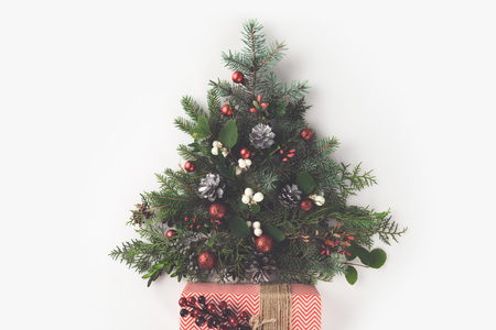 top view of christmas tree made of fir branches, christmas balls and pine cones with present, isolated on white Zdjęcie Seryjne