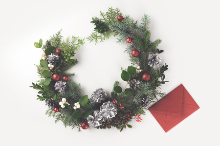 top view of christmas wreath made of fir branches, christmas balls and pine cones with red envelope, isolated on white Zdjęcie Seryjne - 89885224