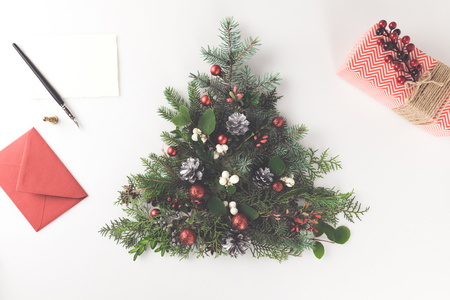 top view of christmas tree made of fir branches, christmas balls and pine cones with letter and present, isolated on white