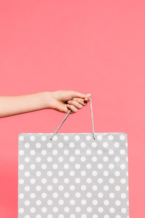 close-up view of hand holding shopping bag isolated on pink Imagens