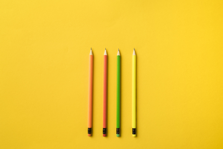 Top view of Four colored pencils with erasers isolated on yellow
