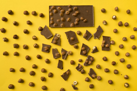 Top view of Chocolate bar with scattered pieces and nuts isolated on yellow  Stock fotó