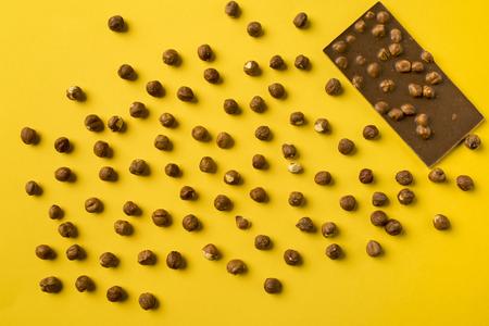노란색에 고립 된 흩어져 견과류와 초콜릿 바의 상위 뷰