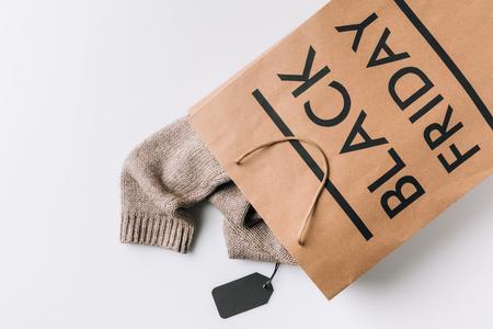 papieren zak met trui binnen en zwarte vrijdag teken op wit oppervlak