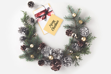 christmas wreath with balls and pine cones, with greeting card, isolated on white