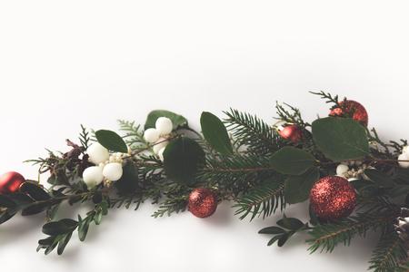 bovenaanzicht van kerstmisspar tak met kerstballen, maretak en dennenappels, geïsoleerd op wit