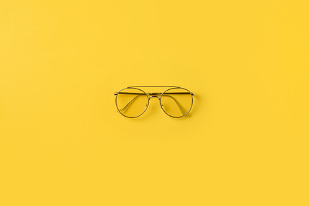 Top view of one stylish Glasses isolated on yellow Imagens