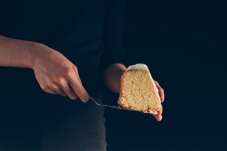 cropped view of female hands holding piece of cake,  isolated on black