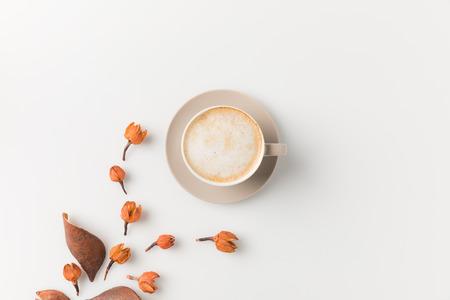 白い表面に美しい花模様のコーヒー カップのトップ ビューの作成