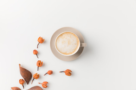top view composition of coffee cup with beautiful flowers on white surface