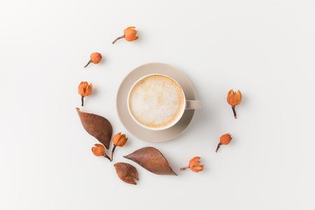 白い面の上の花に囲まれたコーヒー カップのトップ ビューの作成 写真素材