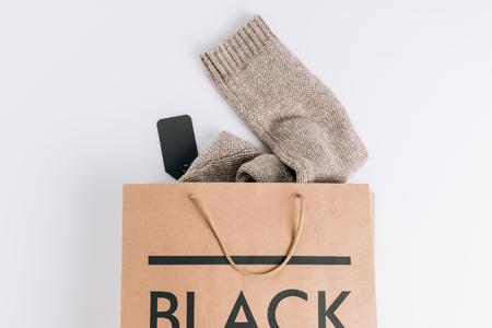 bolsa de papel con suéter dentro y letrero negro sobre superficie blanca Foto de archivo