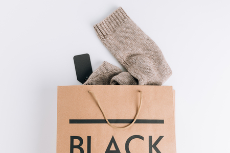 papieren zak met trui binnen en zwart bord op wit oppervlak Stockfoto