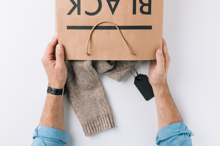 top view of man holding paper bag with sweater inside and black sign on white surface
