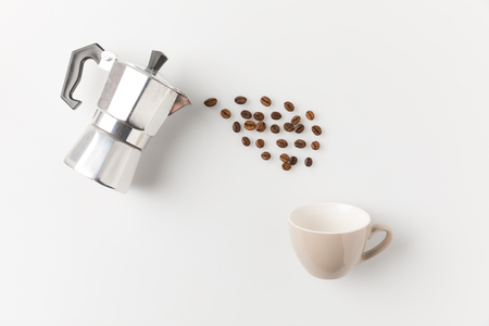 composition of coffee beans pouring from pot into cup on white surface