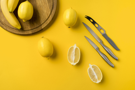 Top view of ripe lemons and knifes isolated on yellow