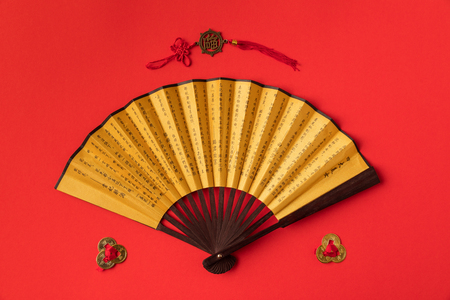 top view of decorative oriental fan and decorations isolated on red