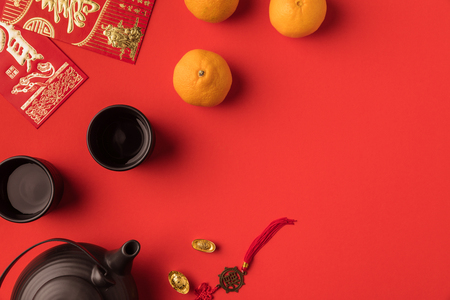 top view of oriental decorations, greeting cards with calligraphy and ceramic tea set isolated on red 免版税图像