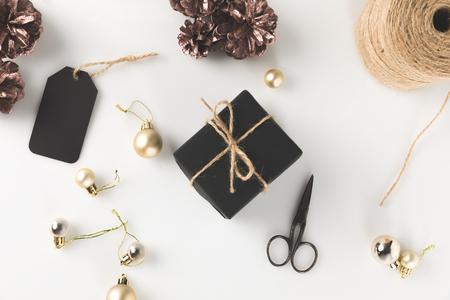 タグ、クリスマス ボール、ハサミ、ひも、白で隔離と黒のクリスマス ギフト ボックスのトップ ビュー 写真素材