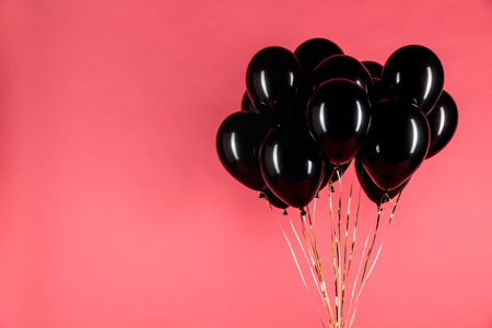 close up view of black shiny balloons isolated on pink