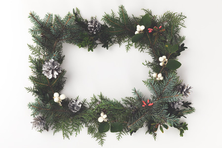 top view of christmas frame made of fir branches, christmas balls, mistletoe and pine cones, isolated on white Zdjęcie Seryjne