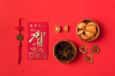 top view of chinese greeting card with calligraphy, oriental decorations and tangerines isolated on red Standard-Bild