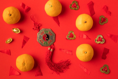top view of golden ingots, oriental decorations and tangerines isolated on red