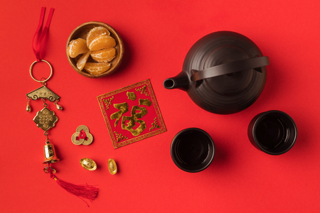 top view of oriental decorations, tangerines and tea set isolated on red  Imagens