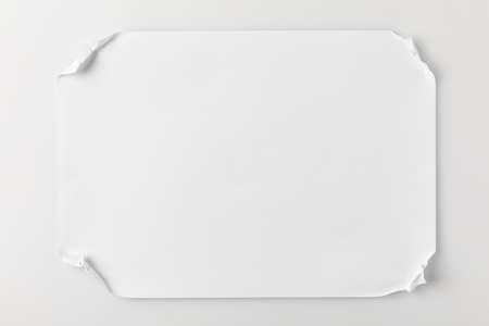 top view of paper with crumpled corners on white table