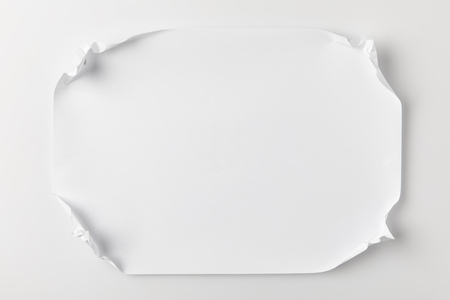 top view of paper with crumpled corners on white surface Stock Photo