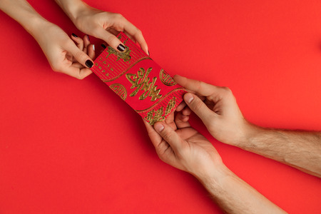 cropped shot of people holding chinese new year greeting card isolated on red Stock Photo - 89887131