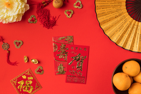 top view of festive chinese decorations and tangerines isolated on red