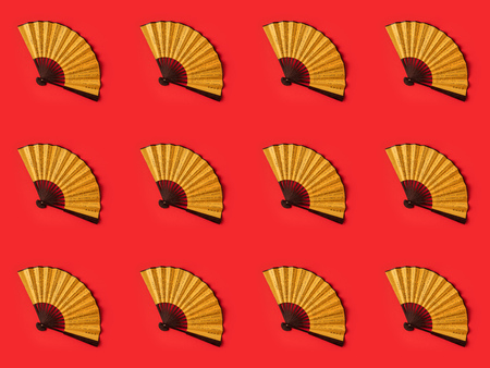 top view of decorative oriental fans pattern isolated on red