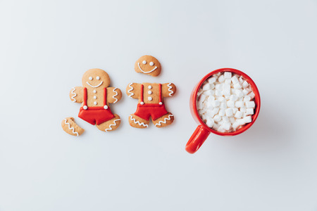 top view of Gingerbread men and cup of hot cacao with marshmallows, isolated on white