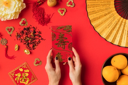 cropped shot of female hands holding greeting card with calligraphy and tangerines with oriental decorations isolated on red
